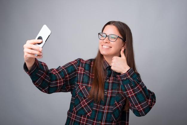 Девушка делает селфи со своим телефоном на сером фоне.