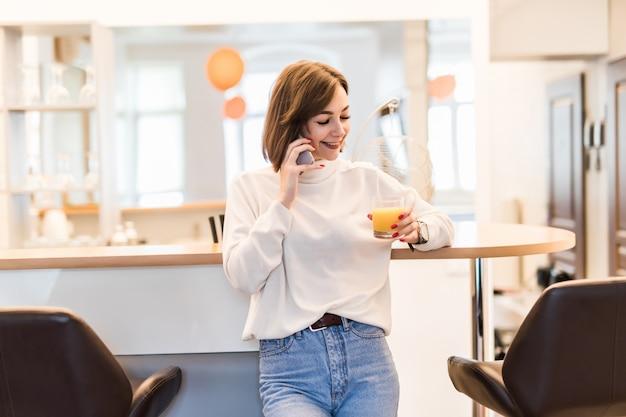 若い女性は電話で話しているとオレンジジュースのガラスを保持しているキッチンのバーの椅子の近くに立っています。