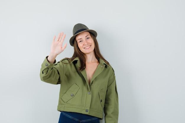 Giovane donna in giacca pantaloni cappello agitando la mano per dire addio e guardando felice