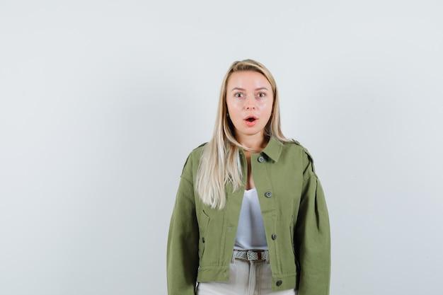 Giovane donna in giacca, pantaloni che guarda l'obbiettivo e guardando meravigliato, vista frontale.