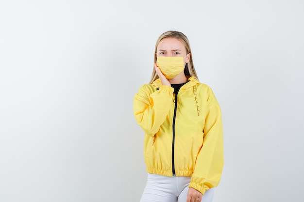 Young lady in jacket, pants, mask suffering from toothache and looking sad , front view.