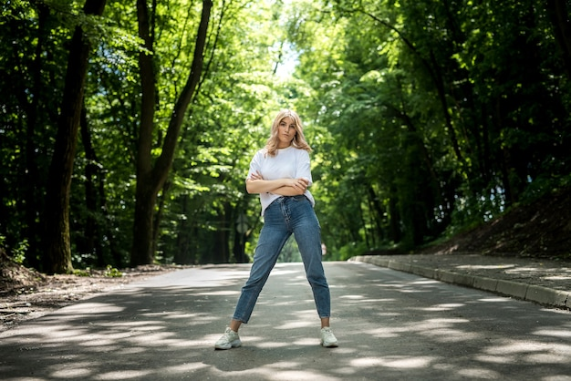 Young lady in jeans and a white t-shirt has a great time in nature in the woods. summer