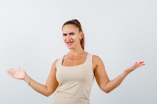 팔을 넓게 유지하는 젊은 아가씨는 탱크 탑에 퍼지고 자신감, 전면보기를 찾고 있습니다.
