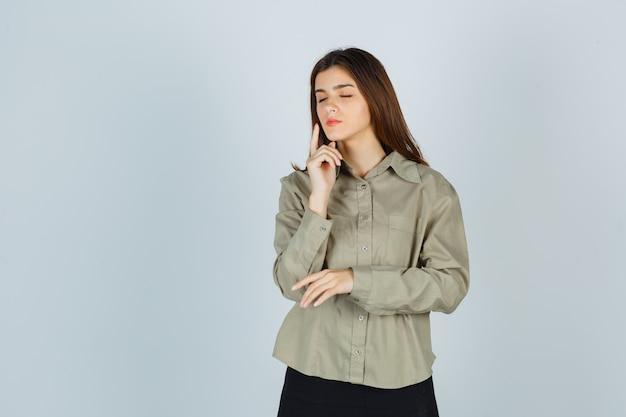 Девушка держит палец возле щеки, закрывает глаза в рубашке, юбке и выглядит спокойно, вид спереди.