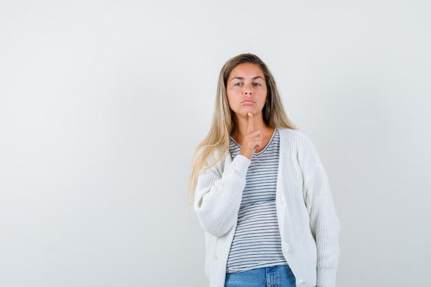 젊은 아가씨 t- 셔츠, 재킷, 청바지에 턱에 손가락을 유지 하 고 불만, 전면보기를 찾고.