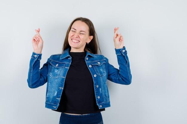 Giovane donna che tiene le dita incrociate in camicetta, giacca e sembra felice. vista frontale.
