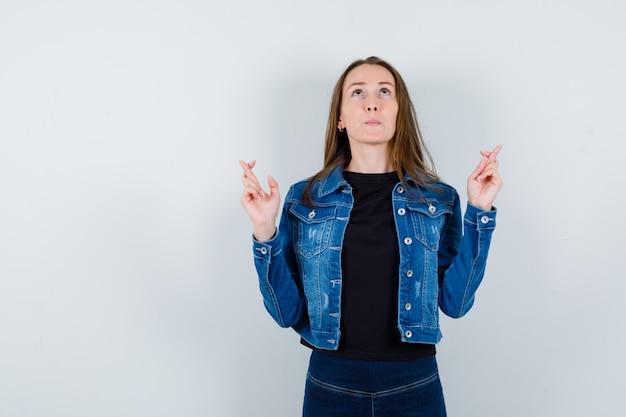 Giovane donna che tiene le dita incrociate in camicetta, giacca e sembra speranzosa, vista frontale.