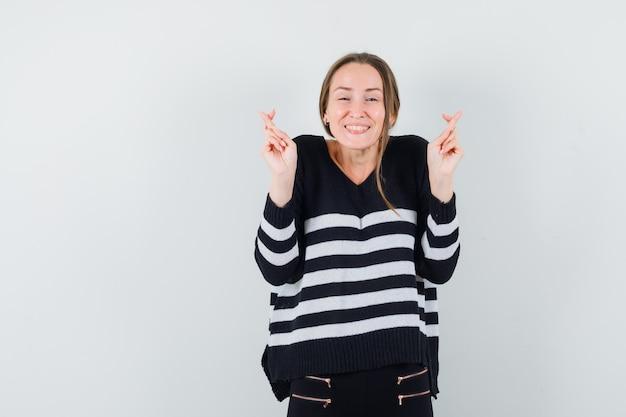 Giovane donna che tiene le dita incrociate in camicia casual e sembra allegra