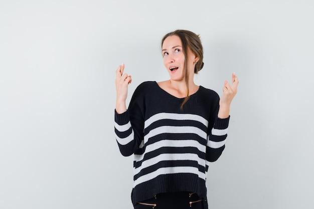 Giovane donna che tiene le dita incrociate in camicia casual e sembra sognante