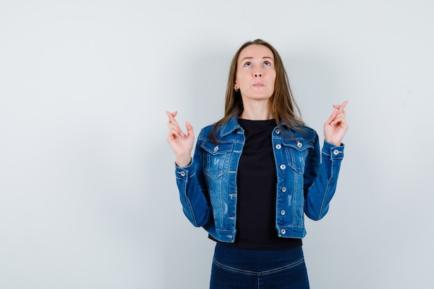 ブラウス、ジャケットで指を交差させて、希望に満ちた正面図を探している若い女性。