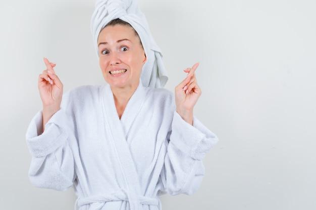 손가락을 유지하는 젊은 아가씨는 흰색 목욕 가운, 수건에 교차하고 즐거운, 전면보기를 찾고 있습니다.