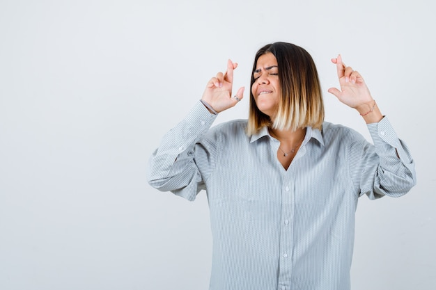 Young lady keeping fingers crossed in oversize shirt and looking happy. front view.