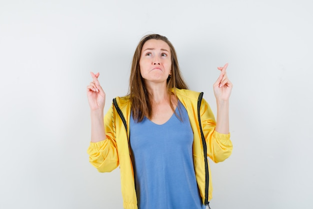 Giovane donna che tiene le dita incrociate in maglietta e sembra triste. vista frontale.