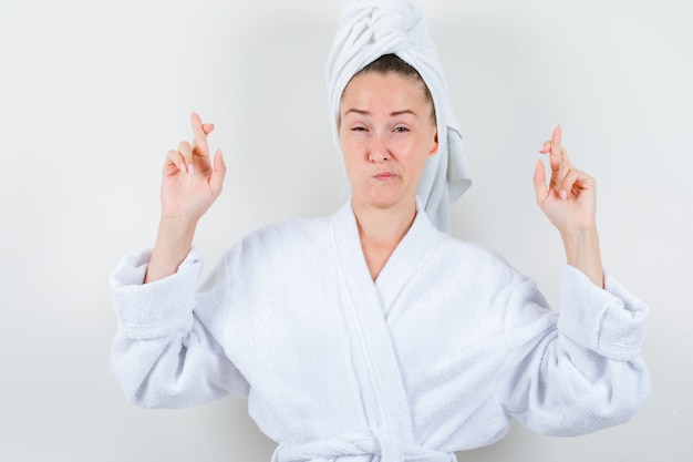 Giovane donna tenendo le dita incrociate in accappatoio bianco, asciugamano e guardando insoddisfatto, vista frontale.