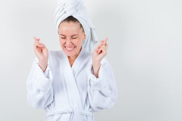Giovane donna che tiene le dita incrociate in accappatoio bianco, asciugamano e sembra felice, vista frontale.