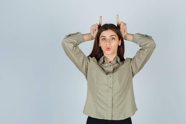 Giovane donna che tiene le dita sopra la testa come corna di toro, fa il broncio con le labbra in camicia e sembra divertente. vista frontale.