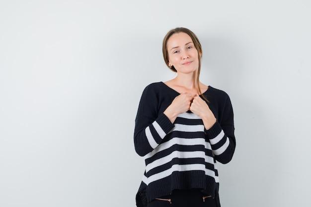 Молодая дама держит кулаки на груди в повседневной рубашке и выглядит мило