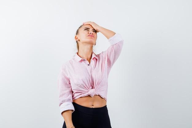 Giovane donna che tiene la mano sulla testa in camicia, pantaloni e sembra triste. vista frontale.