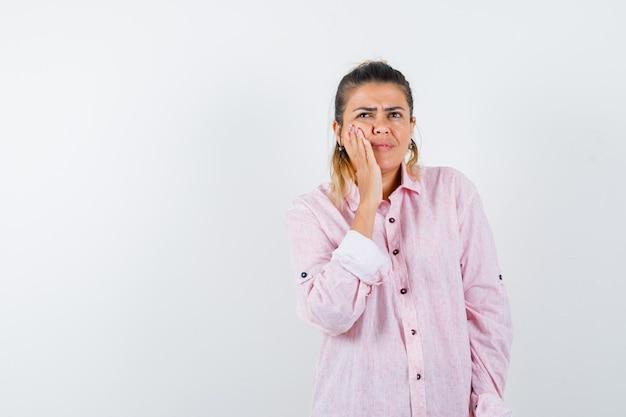 Девушка в розовой рубашке держит руку на щеке и выглядит взволнованной