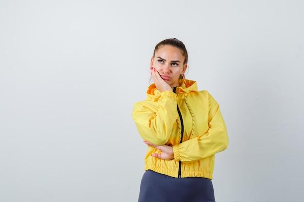 黄色いジャケットで頬に手を保ち、夢中になっている、正面図を探している若い女性。