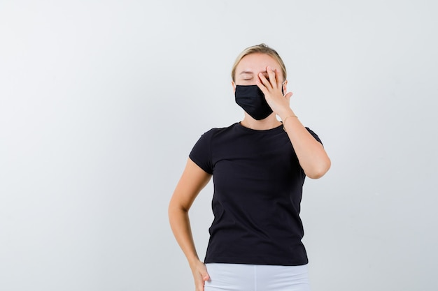 검은 색 t- 셔츠, 마스크에 눈에 손을 유지 하 고 잠겨있는, 전면보기를 찾고 젊은 아가씨.
