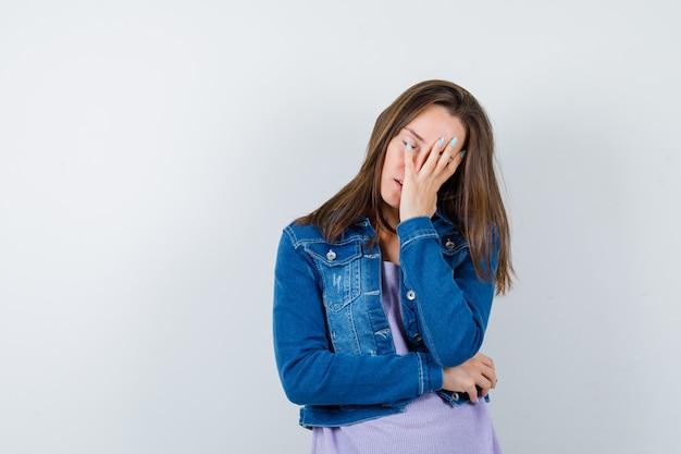 Tシャツ、ジャケット、苦しそうな顔、正面図で手をつないでいる若い女性。