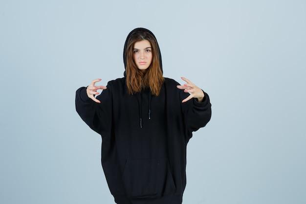 Giovane donna che tiene le mani in modo aggressivo in felpa con cappuccio oversize, pantaloni e sembra infastidita. vista frontale.