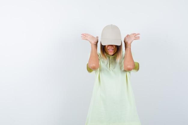 Giovane donna che tiene le mani in modo aggressivo in t-shirt, berretto e sembra infastidita. vista frontale.