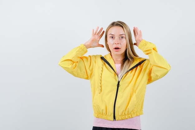 Young lady keeping hands in aggressive manner in t-shirt, jacket and looking annoyed