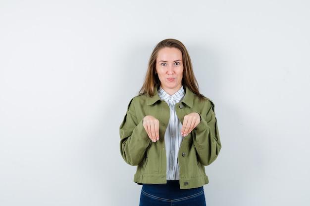 シャツ、ジャケット、おかしい、正面図で胸の上に足として手を保持している若い女性。