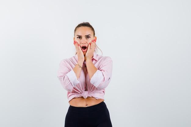 Giovane donna che tiene le mani sulle guance in camicia, pantaloni e sembra scioccata
