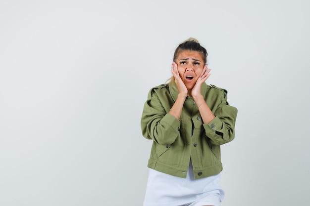 Giovane donna che tiene le mani sulle guance in giacca di t-shirt e sembra dispiaciuta