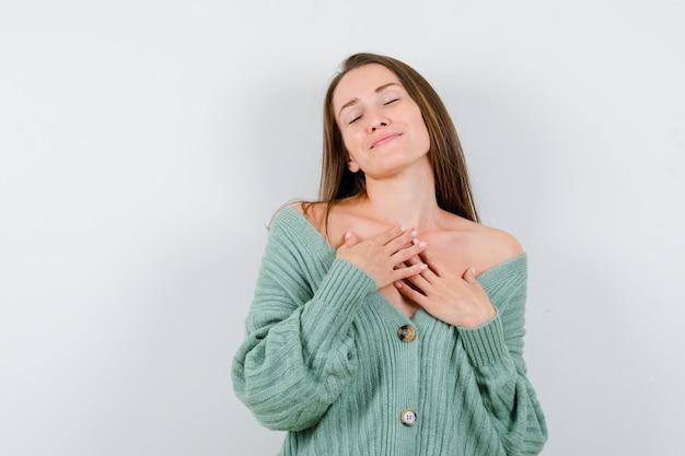 Giovane donna che tiene le mani sul petto in cardigan di lana e sembra grata. vista frontale.