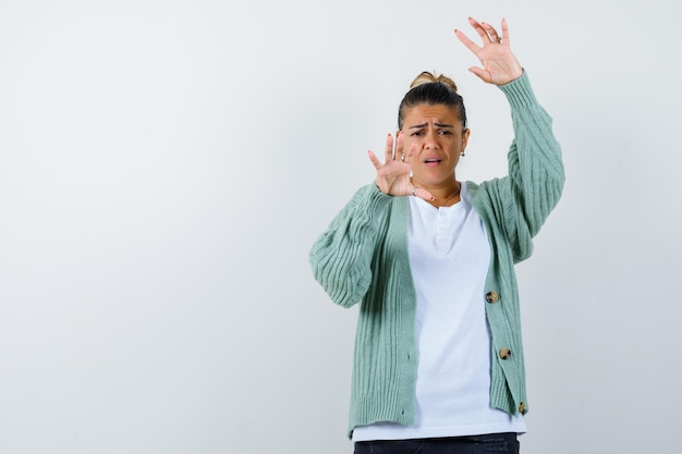Young lady keeping hands in defend pose in t-shirt, jacket and looking scared
