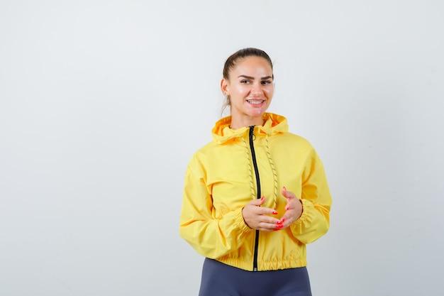 Giovane donna che tiene le mani davanti a sé in giacca gialla e sembra allegra. vista frontale.