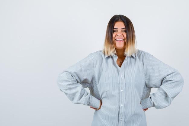 Giovane donna che tiene le mani sui fianchi in una camicia oversize e sembra carina, vista frontale.