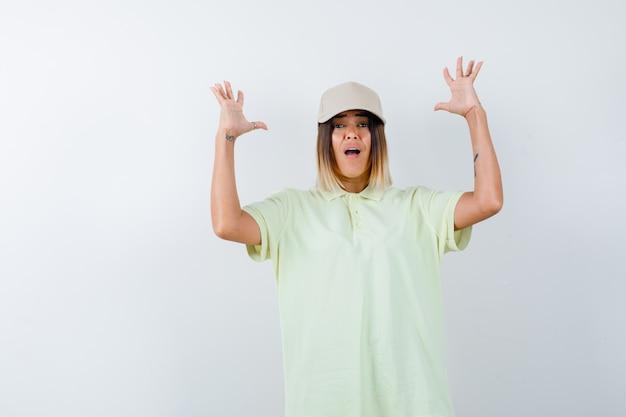 젊은 아가씨 t- 셔츠, 모자에 공격적인 방식으로 손을 유지 하 고 스트레스, 전면보기를 찾고.