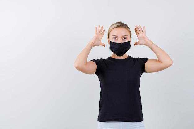 티셔츠, 바지, 의료 마스크에 공격적인 방식으로 손을 유지하는 젊은 아가씨