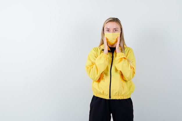 トラックスーツ、マスクで口の近くに手を保ち、驚いて見える若い女性。正面図。