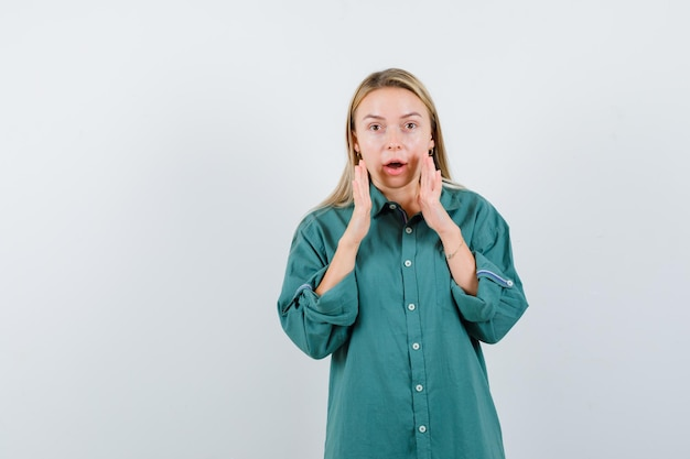 녹색 셔츠에 열린 입 근처에 손을 유지하고 놀란 젊은 아가씨