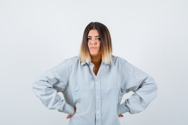 特大のシャツを着て腰に手を当てて自信を持って見ている若い女性、正面図。