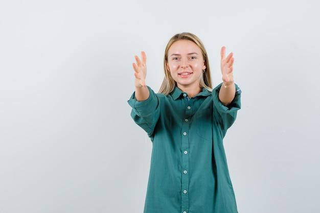 녹색 셔츠에 뻗은 손을 유지하고 쾌활한 찾고 젊은 아가씨