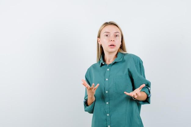 Giovane donna che tiene le mani in un gesto perplesso in camicia verde
