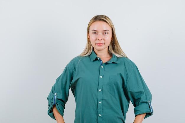 Giovane donna che tiene le mani sulla vita in camicia verde e sembra sicura