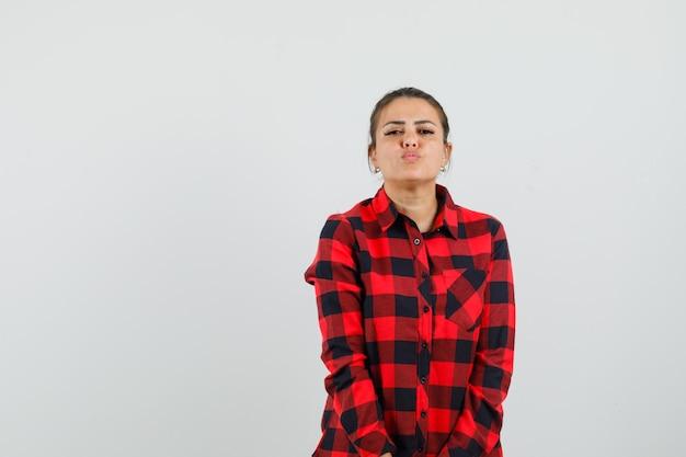 Giovane donna che mantiene le labbra piegate in camicia a quadri e sembra allettante