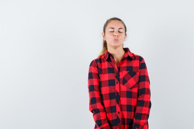 チェックのシャツに唇を折りたたんで、魅力的に見える若い女性