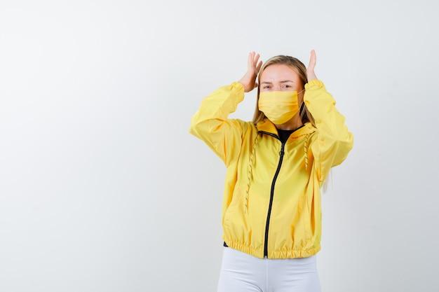 ジャケット、ズボン、マスクで頭の近くで手を上げて、後悔している若い女性。正面図。