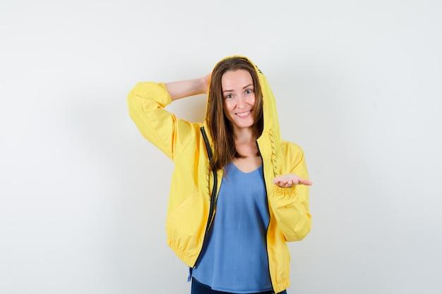 上げられた手のひらをtシャツ、ジャケットで開いたままにし、自信を持って見える若い女性