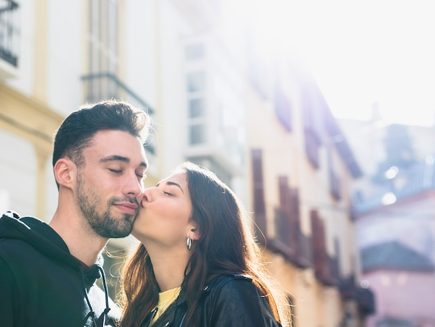 Young lady kissing positive guy on street