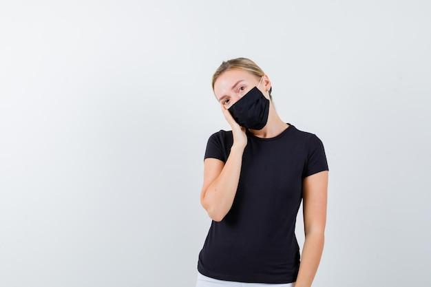Giovane donna che si appoggia la guancia a portata di mano in maglietta, pantaloni, maschera medica e sembra pensierosa
